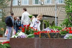 Menina que coloca flores à chama eterno no quadrado dos lutadores caídos em Volgograd Fotos de Stock Royalty Free