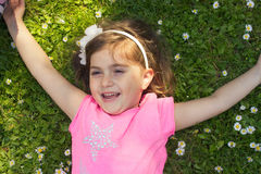Menina que coloca na grama Fotos de Stock