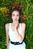Menina que coloca no prado Imagens de Stock Royalty Free
