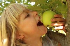 Menina que come Apple na árvore Foto de Stock