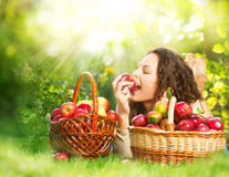 Menina que come Apple orgânico no pomar Imagens de Stock Royalty Free