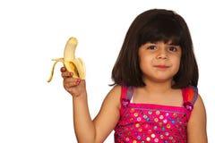 Menina que come a banana Foto de Stock