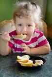 Menina que come a banana e a maçã Fotos de Stock Royalty Free