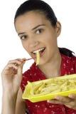 Menina que come batatas imagens de stock