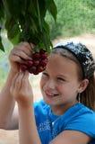 Menina que come cerejas fora da árvore fotografia de stock royalty free