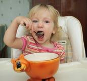 A menina que come com uma colher Imagem de Stock