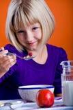 Menina que come cornflakes Foto de Stock