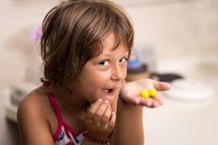 Menina que come doces amarelos Fotografia de Stock