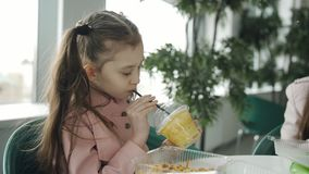 Menina que come em macarronetes de um café e no suco de cenoura bebendo de uma palha A menina bebe o suco de um copo plástico n vídeos de arquivo