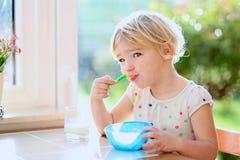 Menina que come a farinha de aveia para o café da manhã Fotos de Stock Royalty Free
