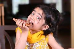 Menina que come a fatia da pizza Foto de Stock Royalty Free