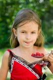 Menina que come a framboesa Imagem de Stock