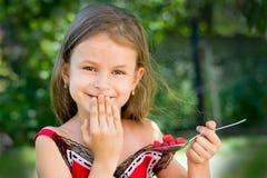 Menina que come a framboesa Fotografia de Stock Royalty Free