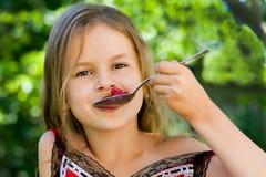 Menina que come a framboesa Imagens de Stock Royalty Free