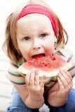 Menina que come a melancia Imagem de Stock