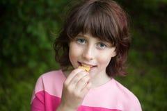 Menina que come microplaquetas Imagem de Stock Royalty Free