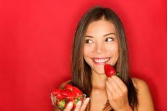 Menina que come morangos Fotos de Stock Royalty Free