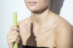 Menina que come o aipo Foto de Stock