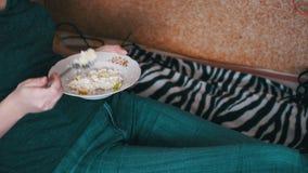 Menina que come o alimento biológico saudável que encontra-se no sofá em casa video estoque