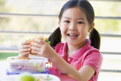 Menina que come o almoço no jardim de infância Fotografia de Stock Royalty Free