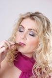Menina que come o bolinho Fotografia de Stock