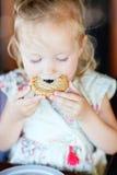 Menina que come o bolinho Imagem de Stock