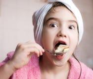 Menina que come o bolo Foto de Stock