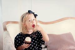 Menina que come o bolo Imagem de Stock