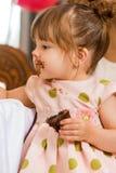 Menina que come o bolo com crosta de gelo em sua cara fotos de stock