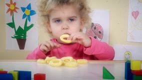 Menina que come o círculo do milho que senta-se perto de seus brinquedos e desenhos da tabela filme