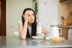 Menina que come o café da manhã na cozinha com dor de cabeça Fotos de Stock Royalty Free