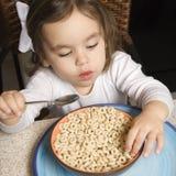 Menina que come o cereal. Imagens de Stock Royalty Free