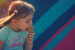 Menina que come o cone de gelado Fotos de Stock Royalty Free