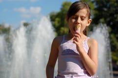 Menina que come o gelado Imagens de Stock