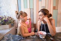 Menina que come o gelado com a mãe no restaurante Foto de Stock
