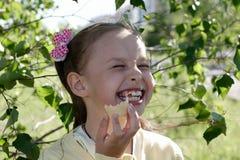 Menina que come o gelado e o riso Fotografia de Stock Royalty Free