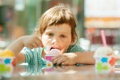 Menina que come o gelado exterior Fotos de Stock