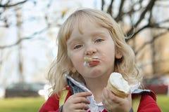 Menina que come o gelado na caminhada Imagem de Stock Royalty Free