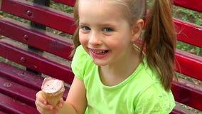 Menina que come o gelado no parque em um banco vídeos de arquivo