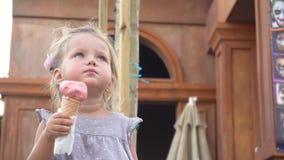 Menina que come o gelado saboroso no parque filme