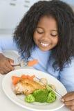Menina que come o jantar da galinha e do vegetal em casa Fotos de Stock Royalty Free