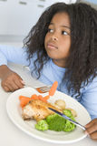 Menina que come o jantar da galinha e do vegetal em casa Fotos de Stock