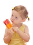 Menina que come o lolly de gelo colorido imagem de stock royalty free