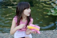 Menina que come o milho Imagens de Stock Royalty Free