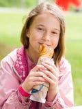 Menina que come o pão Foto de Stock Royalty Free