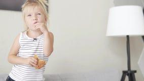 Menina que come o pão branco Criança com fome apenas em casa