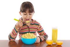 Menina que come o pequeno almoço Fotografia de Stock