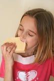 Menina que come o queijo Fotos de Stock Royalty Free