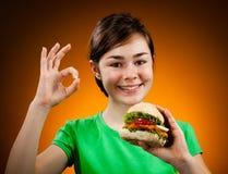 Menina que come o sanduíche grande que mostra o sinal APROVADO Imagem de Stock