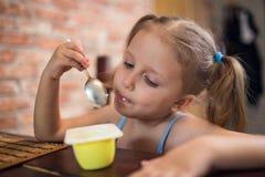 Menina que come o yogurt Imagens de Stock Royalty Free